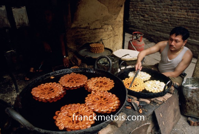 "In a street, a man is cooking ""jalebi"". Nepal. ""Jalebi"" is a very popular sweet in South Asia."